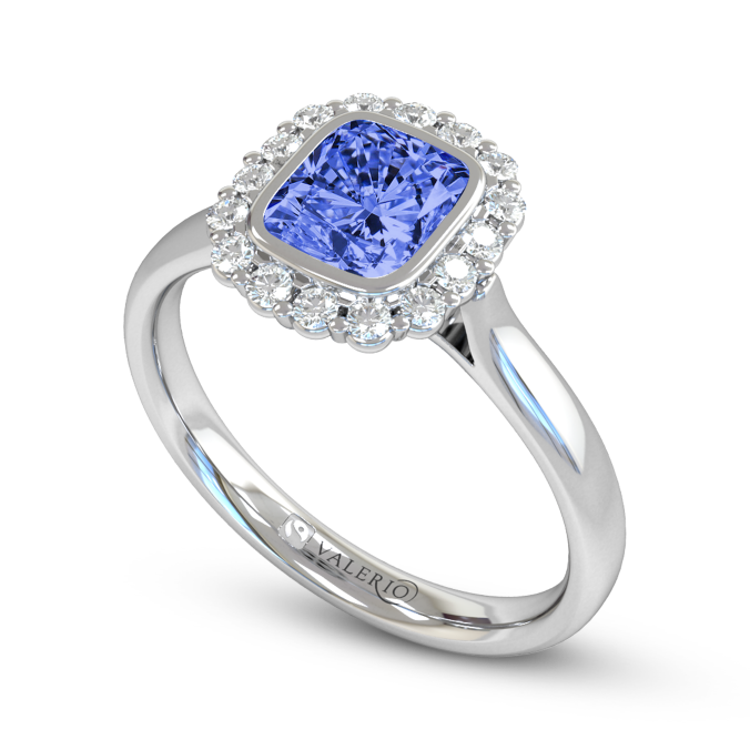 Valerio Jewellery ethically sourced tropical blue sapphire and diamond cluster engagement ring. The vivacious colour of this King of gemstones is a treasure to delight over. The tapered daylight shoulder shank is available in 18k Fairtrade yellow, white and rose gold. The 0.75ct. centre stone can be changed to match the birth stone of the wearer.