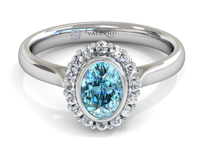 The Valerio Aquamarine Halo ladies ethical engagement ring echoes warm tropical blue seas. The oval cut Madagascan centre stone dances with fourteen vivacious ethical diamonds. Set in 18k white, yellow or rose Fairtrade Gold, the tapered daylight shoulders carries March's birthstone like a princess with her courtiers.
