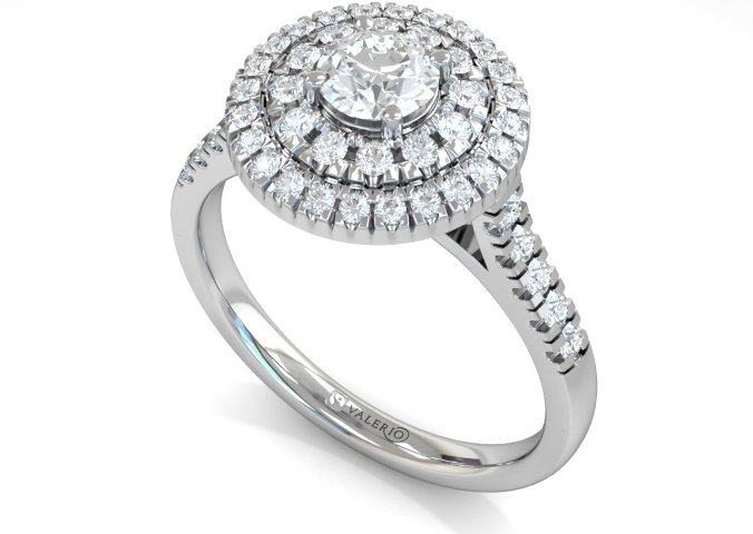 Brilliant cut diamond cluster ethical engagement ring is encircled by two rows of accompanying diamonds. A truly exceptional diamond ring destined for an exceptional loved one. The claw set daylight shoulder shank is lined with diamond and available in 18k Fairtrade Gold.